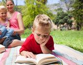 Poważne mały chłopiec czytanie podczas pikniku z rodziną — Zdjęcie stockowe