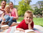 Smiling little boy reading lying on the grass while having a pic — Stock Photo