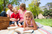 Blond girl reading lying on a picnic tablecloth — Stock Photo