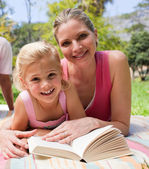 Happy mother and her daughter reading in a park — Foto de Stock