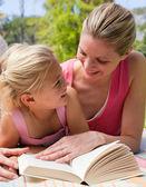 Portrait d'une mère souriante et sa fille à un picni de lecture — Photo