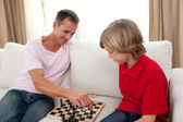 Attentive father playing chess with his son — Stock Photo