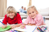 Lively siblings drawing lying on the floor — Stock Photo