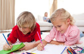 Adorable siblings drawing lying on the floor — Stock Photo