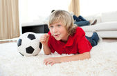 Excited boy watching football match lying on the floor — Stock Photo