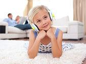 Adorable little girl listening music lying on the floor — Stock Photo