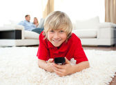 Smiling boy watching TV lying on the floor — Stock Photo