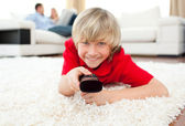 Jolly boy watching TV lying on the floor — Stock Photo