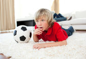 Animated boy watching football match lying on the floor — Stock Photo