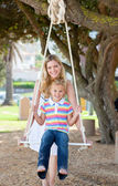 Caring mother pushing her daughter on a swing — Stock Photo