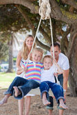 Joyful parents pushing their children on a swing — Stok fotoğraf