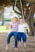 Adorable siblings swinging — Stock Photo