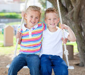Cute siblings swinging — Stock Photo
