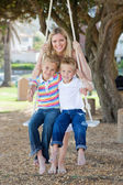 Smiling mother and her children swinging — Stock Photo