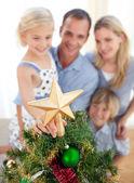Ojciec podnoszenia jego córka postawić boże narodzenie gwiazda na — Zdjęcie stockowe