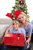 Portrait of a mother and her son holding Christmas gift — Stockfoto
