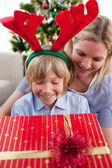 Smiling mother and her son opening Christmas present — Stock Photo