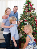 Portrait of a young family decorating a Christmas tree — Stock Photo