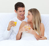 Intimate couple drinking orange juice lying on their bed — Stock Photo