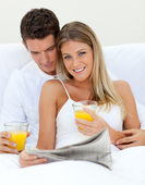 Loving couple reading a newspaper and drinking orange juice — Stock Photo