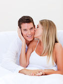 Intimate woman kissing her husband sitting on bed — Stock Photo