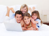 Smiling family looking at a laptop lying down on bed — Stock Photo