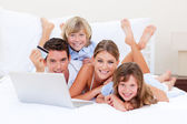 Enthusiastic family buying online lying down on bed — Stock Photo