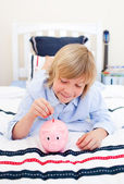 Cute boy inserting a coin in a piggybank lying down on bed — Stock Photo