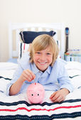 Smiling boy inserting a coin in a piggybank lying down on bed — Stock Photo