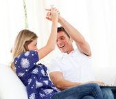 Mirthful couple using a laptop sitting on sofa — Stock Photo
