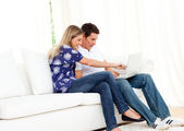 Merry couple using a laptop sitting on sofa — Stock Photo