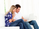 Animated couple using a laptop sitting on sofa — Stock Photo