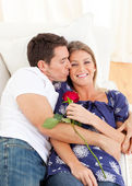 Affectionate man kissing his wife lying on sofa — Stock Photo