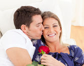Portrait of a charming man kissing his wife lying on sofa — Stock Photo