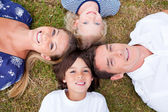 Cheerful family lying in circle on the grass — Stock Photo