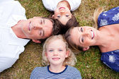 Loving family lying in circle on the grass — Stock Photo