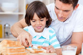 Loving father and his son spreading jam on bread — Stock Photo