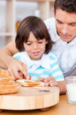 Affectionate father and his son spreading jam on bread — Stock Photo