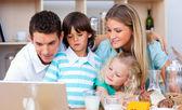 Schöne familie mit laptop während dem frühstück — Stockfoto