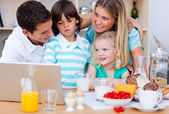 Blissful family using laptop during the breakfast — Stock Photo