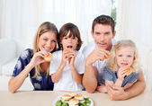 Enthusiastic family eating burgers in the living room — Stock Photo