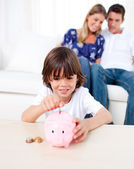 Joyful little boy inserting coin in a piggybank in the living ro — Stock Photo