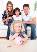 Blond little girl inserting coin in a piggybank — Stock Photo