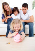 Adorable little girl inserting coin in a piggybank — Stock Photo