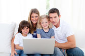 Portrait of a joyful family using a laptop sitting on sofa — Stock Photo