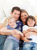Caucasian family watching television sitting on sofa — Stock Photo