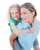 Caucasian mother giving her daughter piggyback ride — Stock Photo