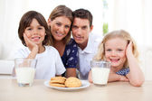 Children eating biscuits and dinking milk with their parents — Stock Photo