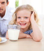 Smiling little girl drinking milk — Stock Photo