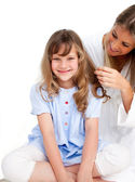 Pretty woman brushing her daugther's hair — Stock Photo